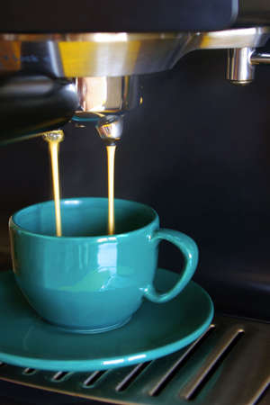 Close up of  espresso coffe machine dispensing coffee into a green coffee cup. Stock Photo - 2426840