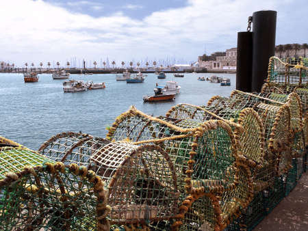 lobster pots: Fishing traps and anchored fishing botes in a port. Cascais, Portugal. Stock Photo