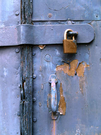 Detail of a old wooden door painted in blue, with metallic padlock and handle. photo