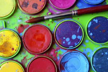 Closeup of messy, used water-color paint-box and paint brush. photo
