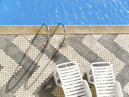 Top view of a swimming pool with two empty white deckchairs.