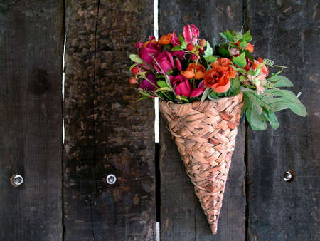 arrangment: Basket with flowers attached in a old wooden fence.