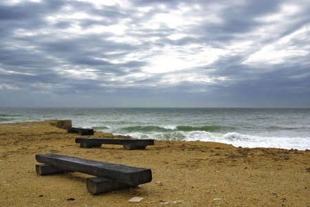 stormy waters: Three wooden benches and stormy sea under deep dark clouds.