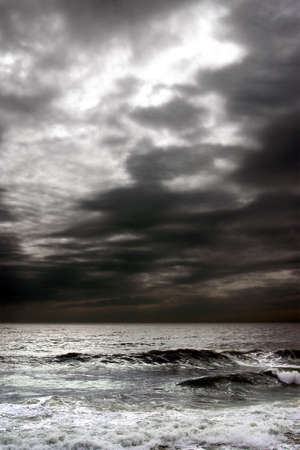 stormy waters: Stormy dark clouds in the sky over troubled ocean.