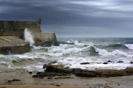 stormy waters: Coastal defence fort under deep dark clouds and stormy sea.