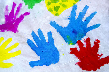Childrens colorful hand prints over white canvas photo
