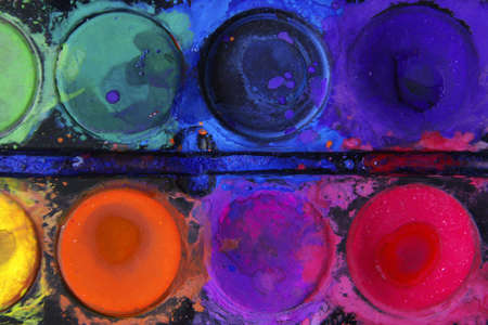 Closeup of messy, used water-color paint-box with black background. Stock Photo