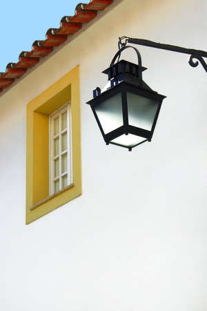 iron curtain: Photo of a white wall with an old typical street-lamp and window