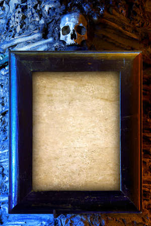 tomb empty: Old wooden frame and empty blank paper hanged on a wall with skull on top Stock Photo