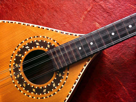 acoustic ukulele: Photo of a acustic mandolin over a red background.
