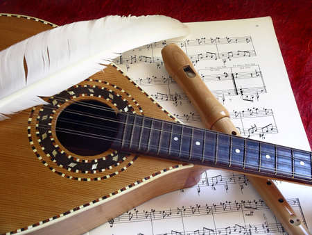 Wooden Mandolin and flute over music partiture photo