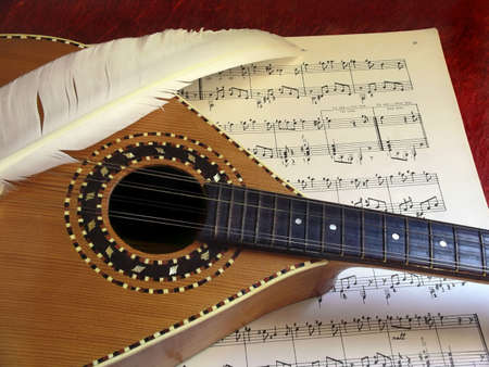Mandolin and white feather over a music partiture. Stock Photo