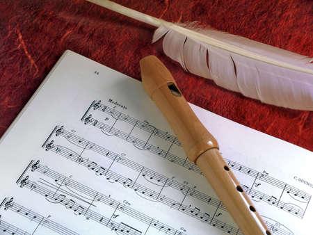 letras musicales: Madera flauta cl�sica y las plumas de blanco sobre una partitura de la m�sica.