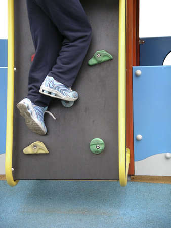 Photo detail of a child climbing a wall in a playground. photo