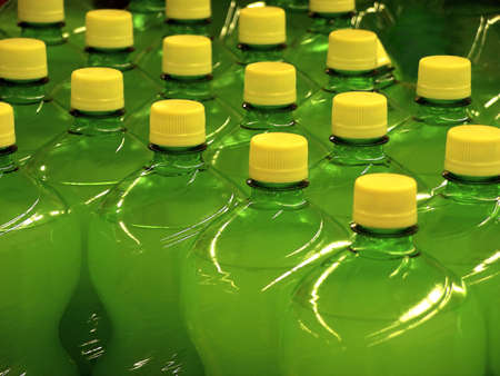 distill: Green bottles with yellow caps aligned in a supermarket.