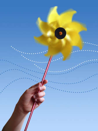 Children's hand holding a yellow toy windmill. Stock Photo - 2426770