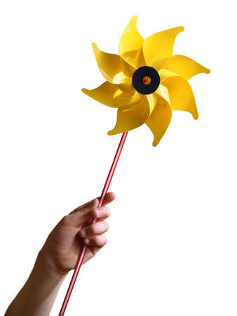 Childrens hand holding a yellow toy windmill, isolated in white background