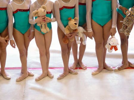 legs apart: Photo of a team of girl gymnasts in a rithmic-gymnastics event.