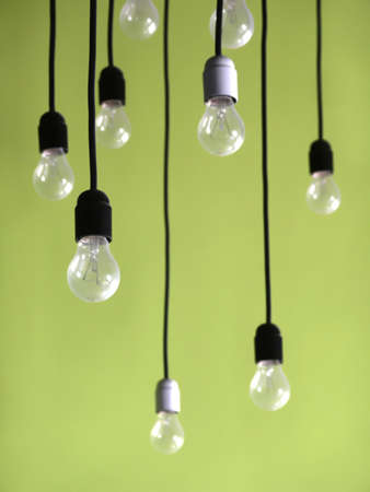 chandeliers: Several light bulbs hanged from the ceiling against a green wall Stock Photo