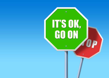 Green traffic sign saying Its OK, go on, in front of regular red STOP sign