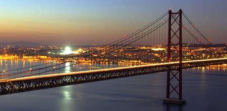 황혼 Tagus 강 및 리스본 도시의 불빛을 통해 브리지의 HDR 사진.