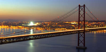 HDR photo of the bridge over Tagus River and Lisbon city lights at dusk.