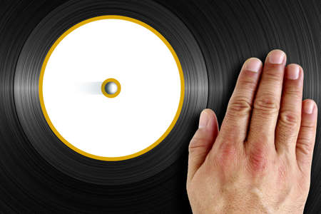 Detail of vinyl record with blank label and DJs hand scratching