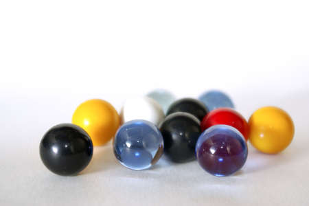 Handful of colorfull glass marbles over white background. photo