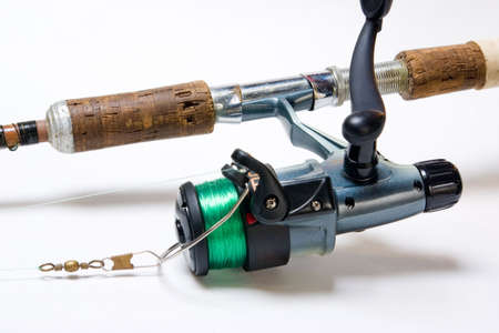 allurement: Detail of fishing rod and reel over white background Stock Photo