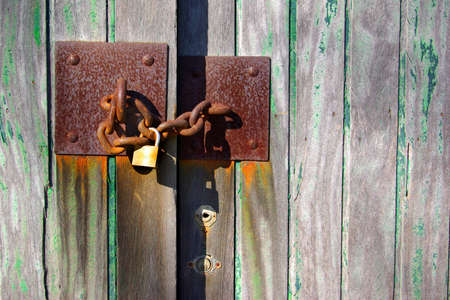 Detail of a old wooden door, with metallic padlock and rusty chain. photo