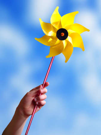Children's hand holding a yellow toy windmill. Stock Photo - 2751502
