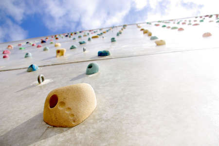 Detail of a climbing wall with a hold in the foreground