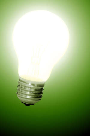 Glowing light bulb turned on over a green background photo