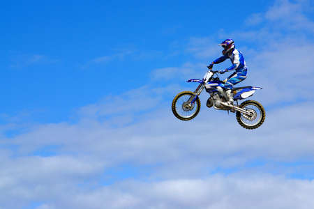 Blue motorcycle and rider jumping in the sky photo