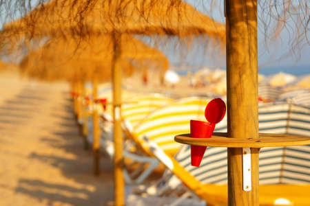 environment concept with red beach ashtray in a beach sunshade photo