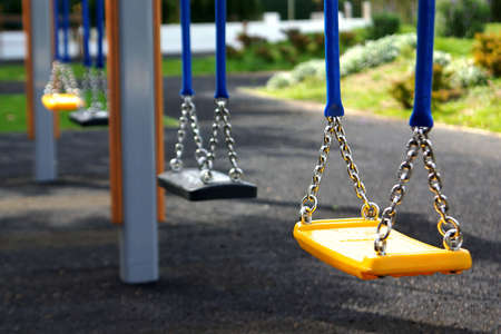 school year: Empty playground swings in a row