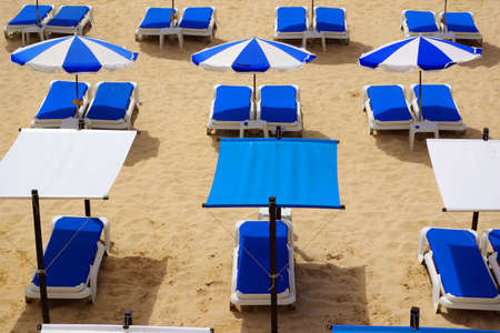 sunshades: Photo of colorful beach sun-shades and deck-chairs Stock Photo