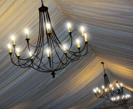 Photo of chandeliers on an tents ceiling in a wedding party photo