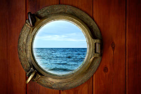 Close-up of a boat closed porthole with ocean view photo