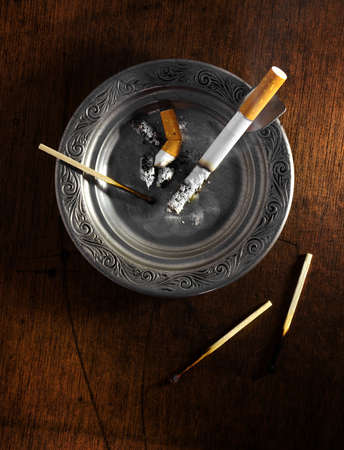 Decorated silver ashtray with cigarette butts and matches over wooden table photo