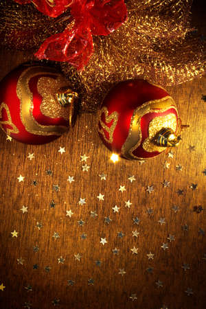 Two red and golden christmas balls and shining little stars over wooden surface