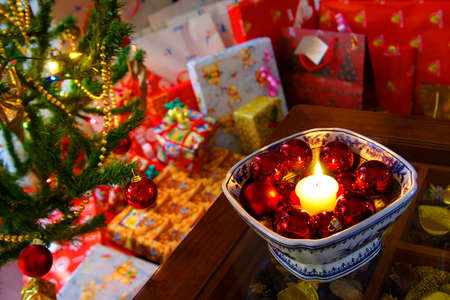 Burning Christmas candles and decorative balls near out of focus presents photo