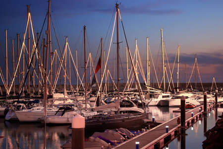 nightfall: Cal scene of a marina with docked yachts at nightfall