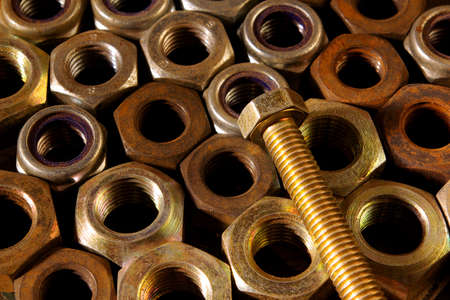 Background of assorted old rusty nuts with a screw on top photo