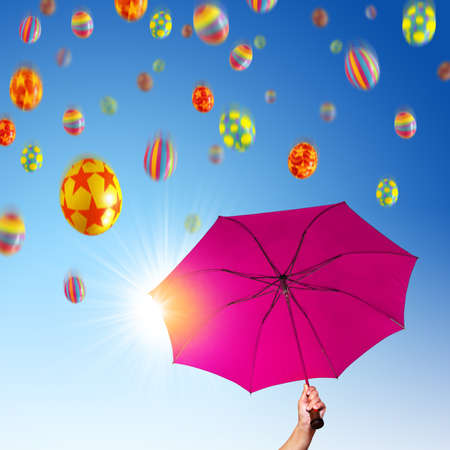 Opened pink umbrella under Easter eggs falling down Stock Photo