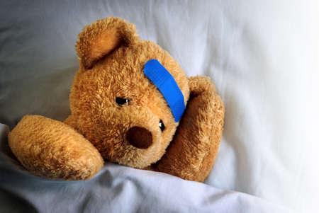 chory: Zdjęcie chory miś z niebieskim bandażem w łóżku
