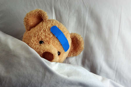 pediatrics: Photo of a sick teddy bear with a blue bandage in bed