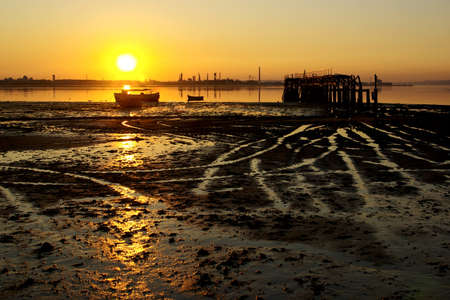 Low tide in a beach with boats and old pier at sunset photo