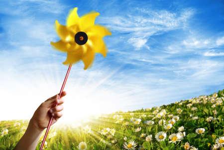 Dzieci strony gospodarstwa żółtym wiatrak w dziedzinie kwiecisty wiosną