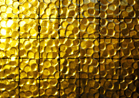 Background of a yellow opaque glass with wire net photo